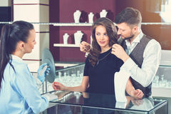 Man trying necklace for his wife at jewelry store. Handsome young men trying necklace for his gorgeous wife at jewelry store. Jeweler in gloves holding mirror Royalty Free Stock Images
