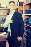 Man is trying on new dark blue jacket. In male clothes store Royalty Free Stock Photos