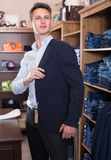 Man is trying on new dark blue jacket. In male clothes store Royalty Free Stock Images