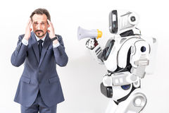 Man is trying not to listen yelling cyborg. Stop yelling. Man wanting to close his ears because of robot holding speaker and he looking at camera with irritation Royalty Free Stock Photos