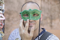 Man trying on one venetian carnival mask Stock Image