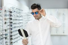 Man trying on sunglasses in optical store Stock Image