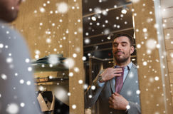 Man trying tie on at mirror in clothing store. Sale, shopping, fashion, style and people concept - happy young man choosing and trying tie on and looking to Royalty Free Stock Photo