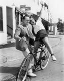 Man trying to balance an exuberant woman on a bicycle Royalty Free Stock Image