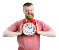 Man trying to break a big alarm clock Royalty Free Stock Photo