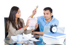 Man trying to break open piggy bank with hammer to get money while woman reluctantly offers it Stock Images