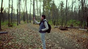 Man trying to catch a connection on his mobile phone in the autumn forest. Autumn forest. A man stands beside the path, trying to catch a connection on his stock video