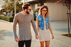 Man trying to cheer up girlfriend while they walking Stock Photos