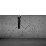 Man trying to climb over wall with business doodles. Isolated in white Stock Photos