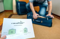 Man trying to close full hand luggage to low cost airlines. Man trying to close full hand luggage for comply low cost airlines restrictions royalty free stock photo