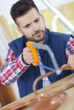Man trying to cut copper pipe with hacksaw. Man trying to cut copper pipe with a hacksaw Royalty Free Stock Images