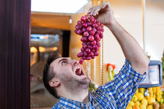 Man trying to eat a bunch of grapes. Stock Photography
