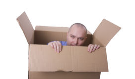 Man trying to escape from a cardboard box Stock Photos