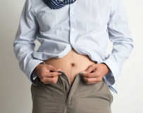 Man trying to fasten pants Stock Photography