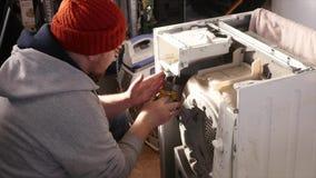Man trying to fix the washing machine stock video