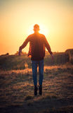 Man trying to fly. Silhouette of jumping man on the field during sunset,selective focus Royalty Free Stock Photo