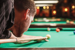 Man trying to hit the ball in billiard. Stock Photo