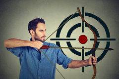 Man trying to hit a target with bow and arrow Royalty Free Stock Photography