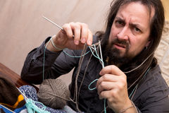 Man is trying to knit Stock Image