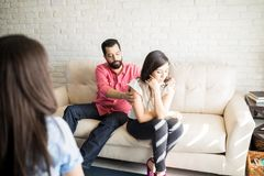 Man trying to make up the conflict with wife during therapy. Young hispanic men trying to make up the conflict with unhappy wife during psychotherapy session stock photos