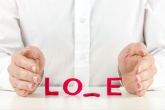 Man trying to nurture a broken relationship. Conceptual image of a man trying to nurture a broken relationship with his hands held protectively around the word stock photos