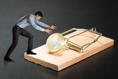Man trying to pick a gold coin Stock Photography