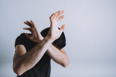 Man trying to protect himself with his arms Stock Images