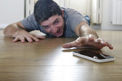 Man trying to reach mobile phone creeping on the ground in smart phone and internet addiction concept Stock Photo