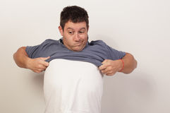 Man trying to remove his shirt Royalty Free Stock Photography