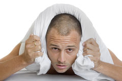 Man Trying to Sleep. Man in bed trying to sleep with a pillow over his ears Stock Photo