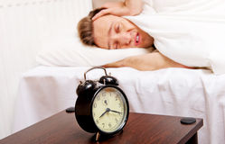 Man trying to sleep, when alarm clock ringing Royalty Free Stock Photography