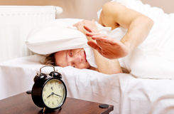 Man trying to sleep, when alarm clock ringing Stock Photo