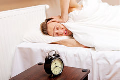 Man trying to sleep, when alarm clock ringing Royalty Free Stock Image