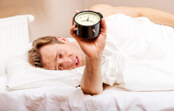 Man trying to sleep, when alarm clock ringing.  Stock Image