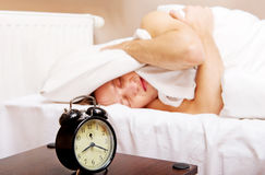 Man trying to sleep, when alarm clock ringing Stock Photography