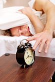 Man trying to sleep, when alarm clock ringing Stock Photos