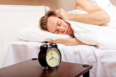 Man trying to sleep, when alarm clock ringing.  Stock Photography