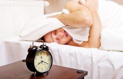 Man trying to sleep, when alarm clock ringing Royalty Free Stock Photo