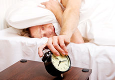 Man trying to sleep, when alarm clock ringing.  Royalty Free Stock Photography