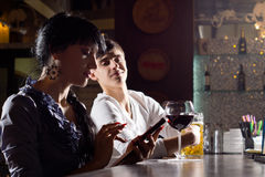 Man trying to sneak a peek at an sms. Man sitting alongside an attractive young women in the bar leaning back with a smile trying to sneak a peek at an sms as royalty free stock images