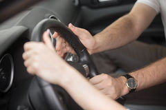 Man trying to take control of the steering wheel Royalty Free Stock Images