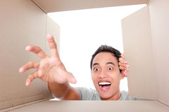 Man trying to take something inside box Stock Photo