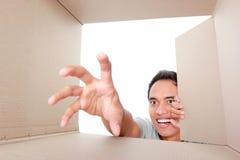 Man trying to take something inside box Royalty Free Stock Photos