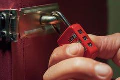 Man trying to unlock combination lock. Closeup photo of a hand  trying to unlock combination lock Stock Photo