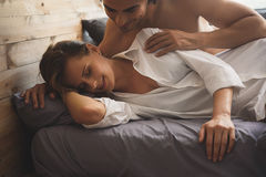 Man trying to wake up his girlfriend. In the morning shirtless guy waking up his girlfriend after a good date Stock Photo