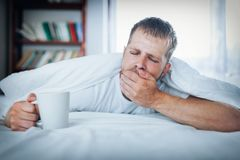 Man trying to wake up in the morning. After night out royalty free stock image