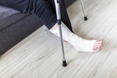 The man is trying to walk with a broken leg. At home stock images