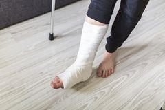 The man is trying to walk with a broken leg. At home stock photos