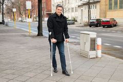 Man trying to walk using crutches Royalty Free Stock Photography