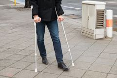 Man trying to walk using crutches Royalty Free Stock Photo